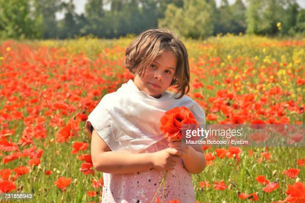 Portrait Of Girl Holding Poppy On Field