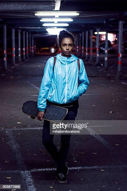 Portrait of girl holding skateboard
