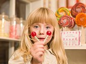 Portrait of girl holding suckers in candy store