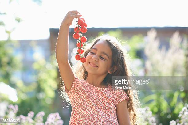 Portrait of girl holding up bunch of cherry tomatoes in garden
