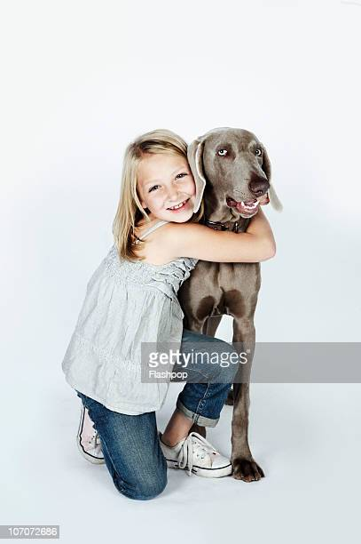 Portrait of girl hugging her pet dog