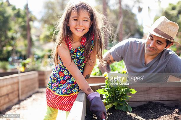 Portrait of girl in community garden planting with father
