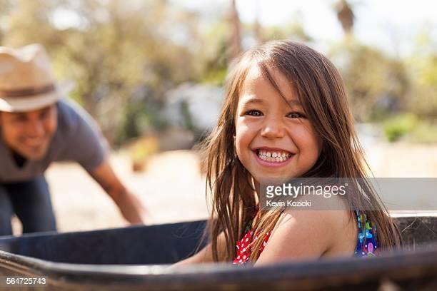 Portrait of girl in community garden riding in wheelbarrow