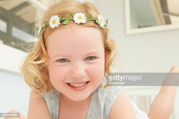 Portrait of girl in daisy chain lying on holiday apartment seat