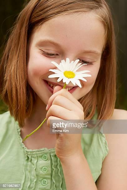 Portrait of girl in garden holding up daisy