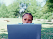 Portrait of girl in park with laptop
