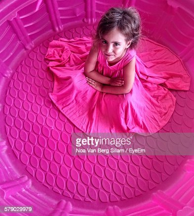 Portrait Of Girl In Pink Dress Sitting In Large Tub