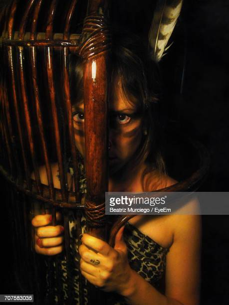 Portrait Of Girl In Tribe Costume Looking Through Wooden Shield At Night
