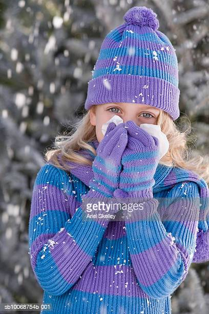 Portrait of girl (6-7) in winter clothing blowing nose, outdoors