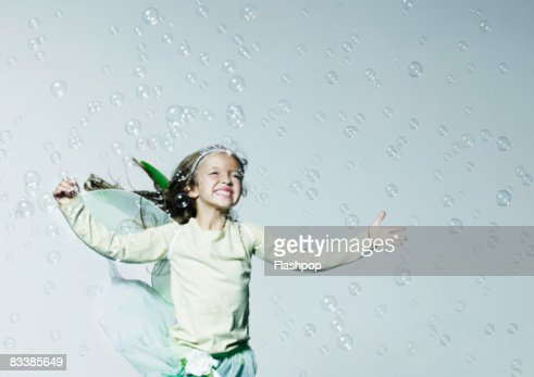 Portrait of girl jumping surrounded with bubbles