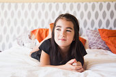 Portrait of girl (8-9) laying on bed