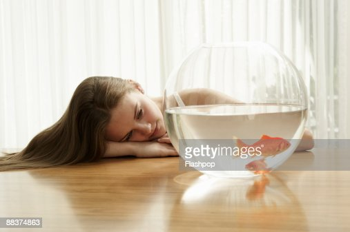 Portrait of girl looking at goldfish : Stock Photo
