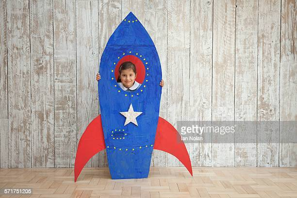 Portrait of girl looking from window of blue homemade  cardboard rocket