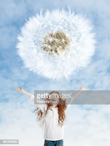 Portrait of girl looking up at dandelion : Stock Photo