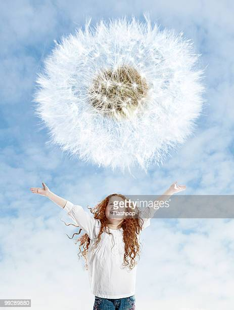 Portrait of girl looking up at dandelion