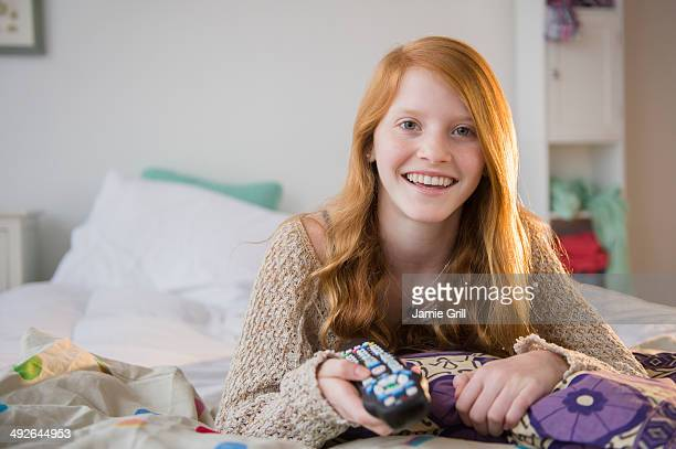 Portrait of girl (12-13) lying on bed, Jersey City, New Jersey, USA