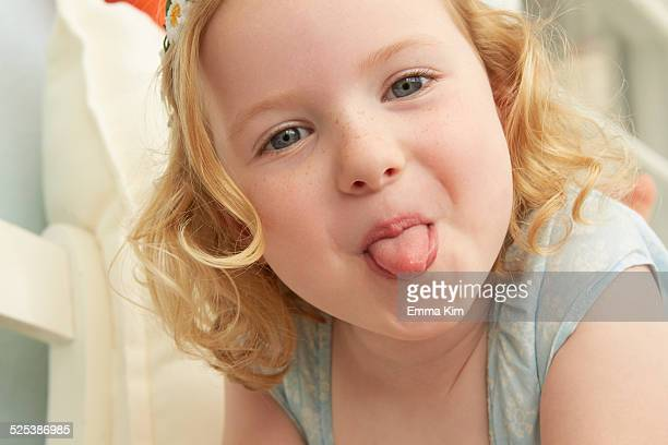 Portrait of girl lying on seat sticking tongue out