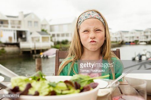 Portrait of girl (8-9) making face at table : Stock Photo