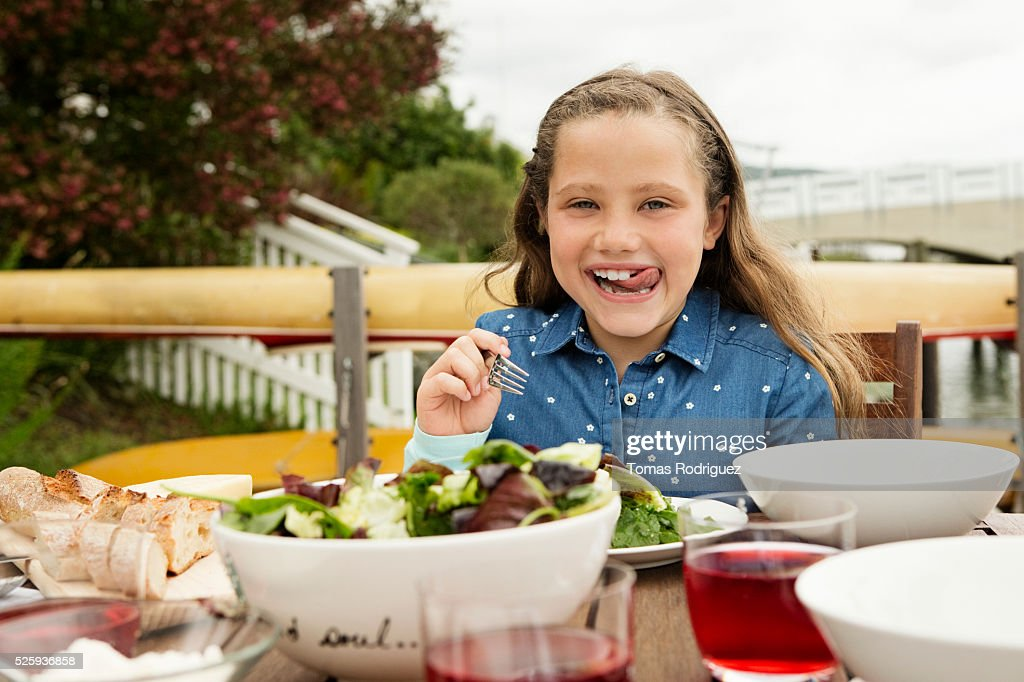 Portrait of girl (6-7) making face at table : Foto stock