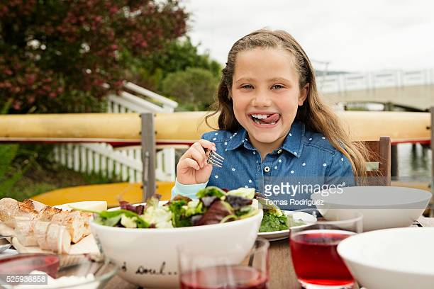 Portrait of girl (6-7) making face at table