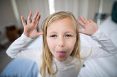 Portrait of girl making facial expression in bedroom at home