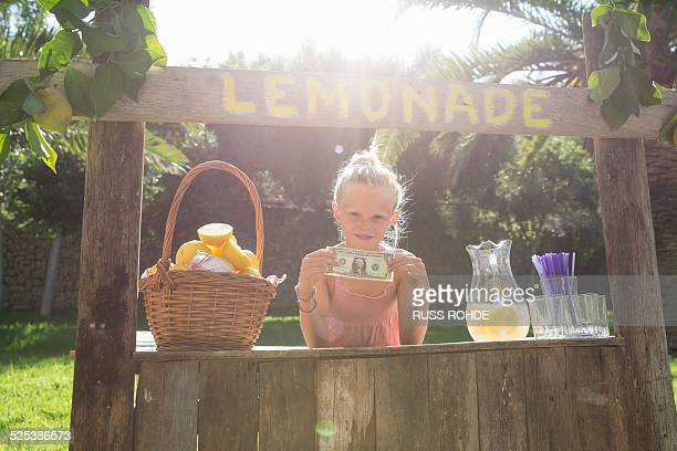 Portrait of girl on lemonade stand holding up one dollar bill