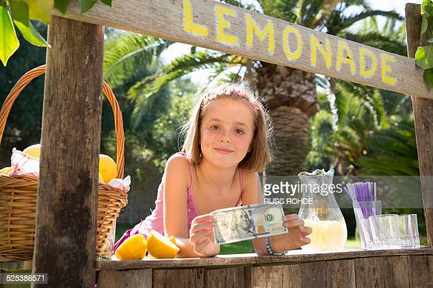 Portrait of girl on lemonade stand holding up one hundred dollar bill
