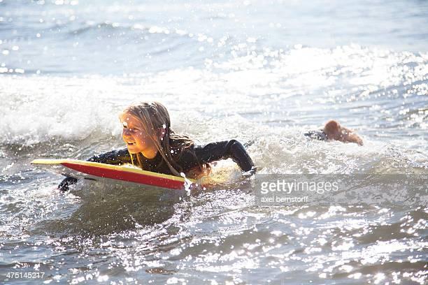 Portrait of girl on surfboard, Wales, UK