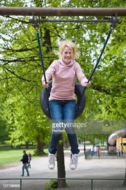 Portrait of girl on swing in park