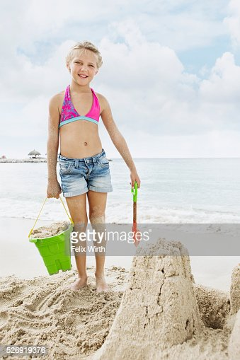 Portrait of girl (10-12) playing on beach in sand : Foto de stock