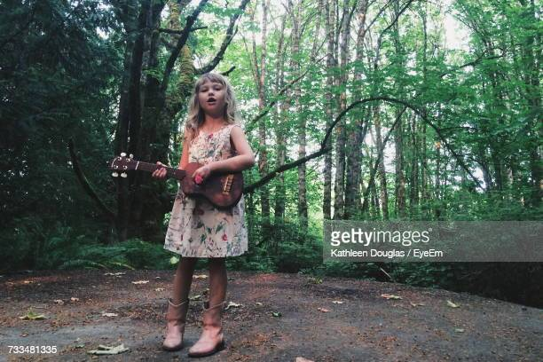 Portrait Of Girl Playing Ukelele In Forest