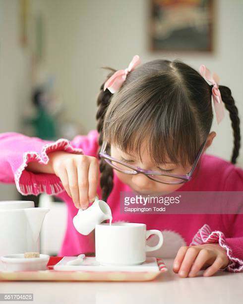 Portrait Of Girl Pouring Milk In Cup