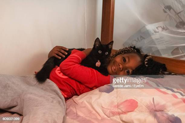 Portrait Of Girl Relaxing With Cat On Bed At Home