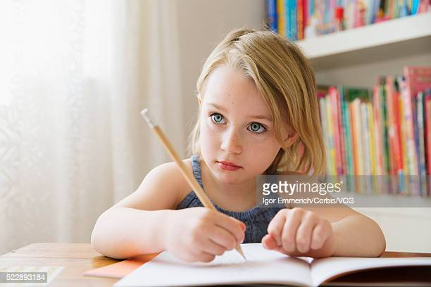Portrait of girl (4-5) sitting at table and drawing