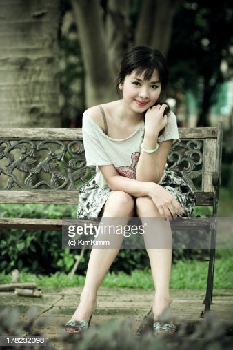 Portrait of girl sitting on bench, hand in hair : Stock Photo