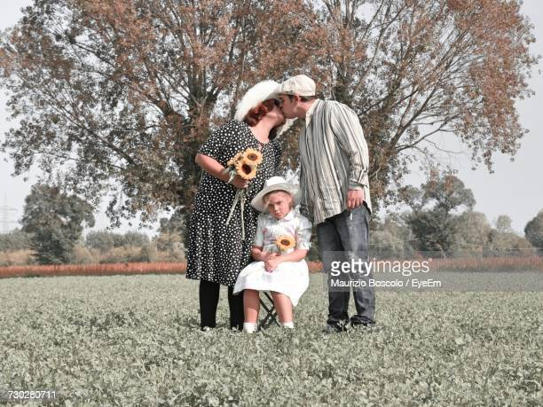 Portrait Of Girl Sitting On Chair While Father And Mother Kissing At Grassy Field Against Tree
