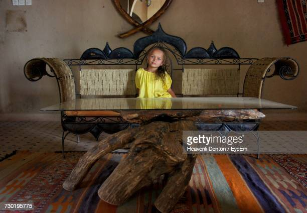 Portrait Of Girl Sitting On Sofa In Living Room