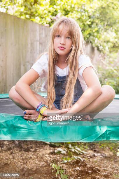 Portrait of girl sitting on trampoline looking at camera