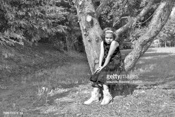 Portrait Of Girl Sitting On Tree At Park