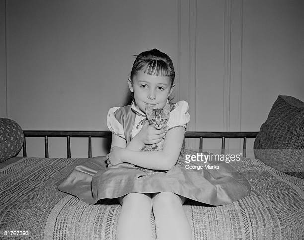 Ritratto di ragazza (10-11) seduta con gattino sul letto