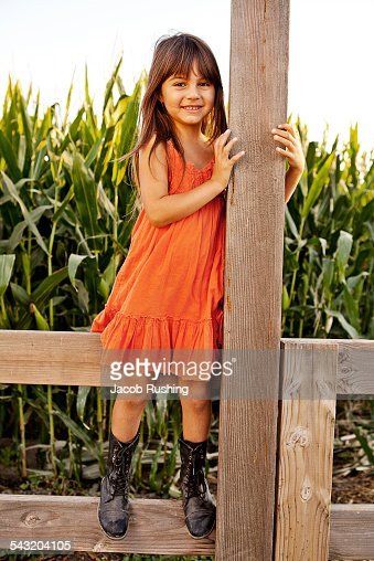 Portrait of girl standing and holding onto field fence