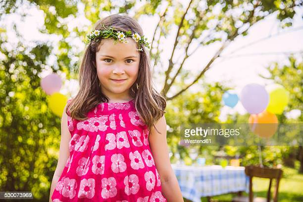 Portrait of girl standing in front of her birthday table in garden