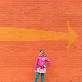 Portrait of girl (12-13) standing in front of orange wall