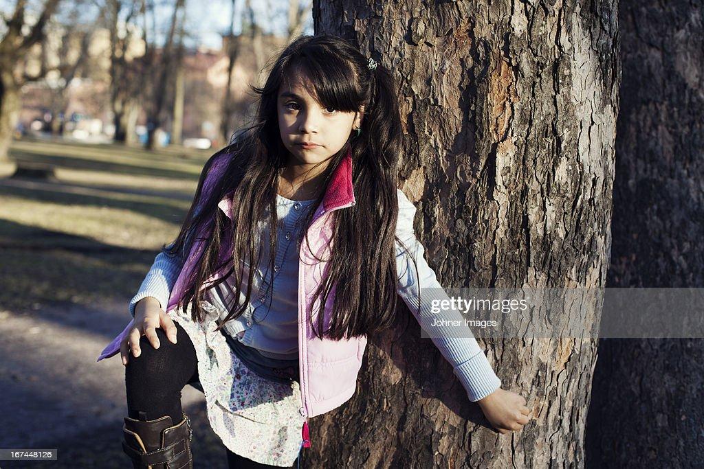 Portrait of girl standing near tree : Stock Photo