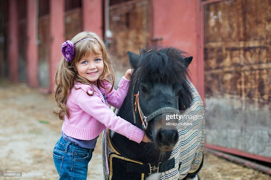 Portrait of girl (4-5) and pony