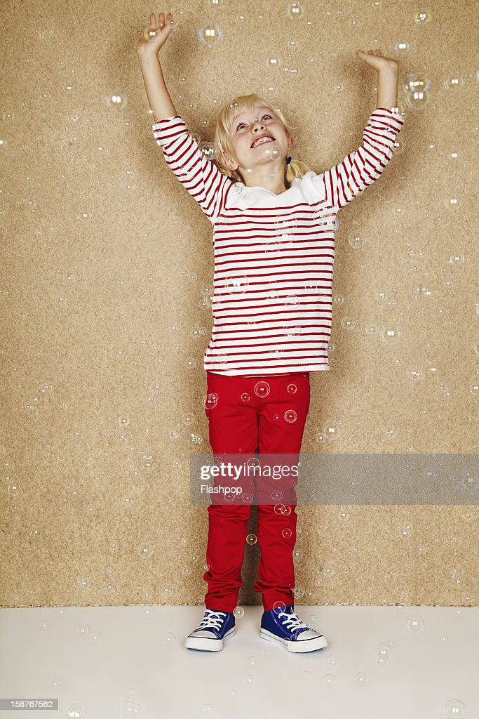 Portrait of girl touching bubbles : Stock Photo