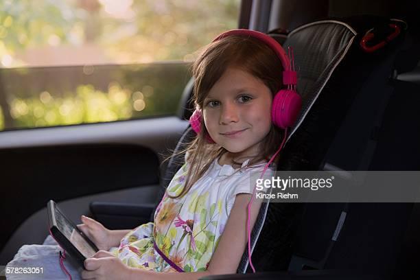 Portrait of girl wearing pink headphones and using digital tablet in car