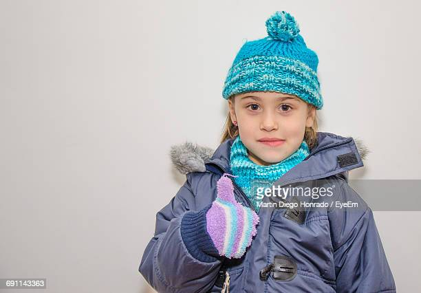 Portrait Of Girl Wearing Warm Clothing Showing Thumbs Up Sign Against White Background