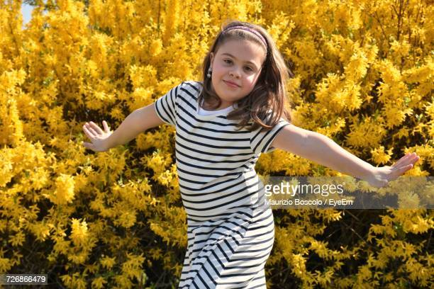 Portrait Of Girl With Arms Outstretched Against Flowering Trees