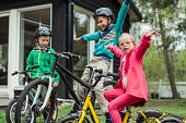 Portrait of girl with arms outstretched riding bicycle with brothers in lawn